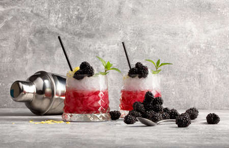 Two glasses with red coctail and ice, blackberries and green leaves of mint, metallic shaker on a grey light background.