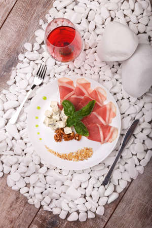 pancetta cubetti: Top view of a plate with prosciutto, Roquefort cheese, walnuts and basil, a glass of red wine on a white stone wooden background. Archivio Fotografico