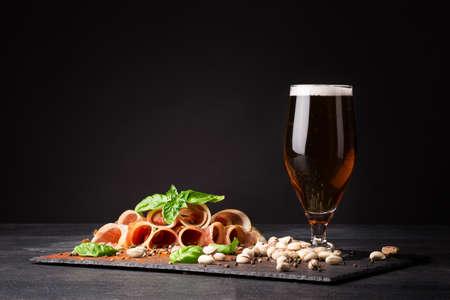 hams: Primer plano de un vaso de humedad lleno de cerveza y espuma blanca, pistachos y rodajas de prosciutto tierno sazonado con pimienta negra y hojas verdes frescas de albahaca sobre un fondo oscuro.
