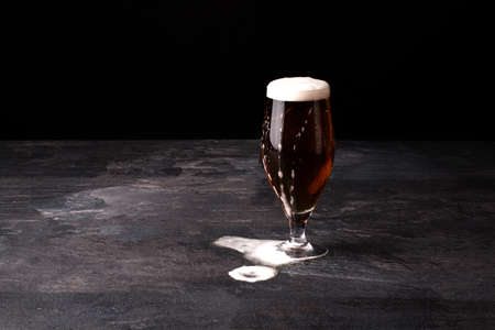 blowed: A big glass of beer full with brown ale and with white foam blowed away on a dark stone background.