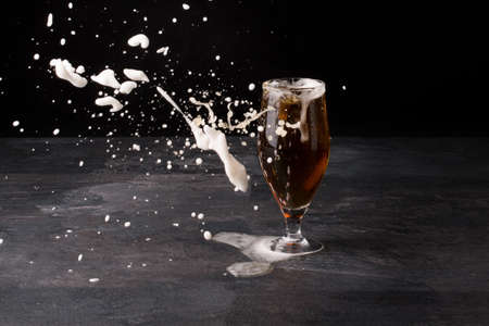blowed: A big glass of beer full with brown ale and with white foam blowed away on a dark stone background. Alcohol beverage.