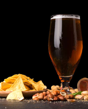 Closeup of moist glass of brown ale, with crisps, bacon, peanuts, hazelnuts, and pistachios on a dark background. Snacks for alcohol drink.