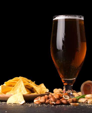hams: Detalle de vaso húmedo de cerveza marrón, con patatas fritas, tocino, cacahuetes, avellanas y pistachos sobre un fondo oscuro. Bocadillos para beber alcohol. Foto de archivo