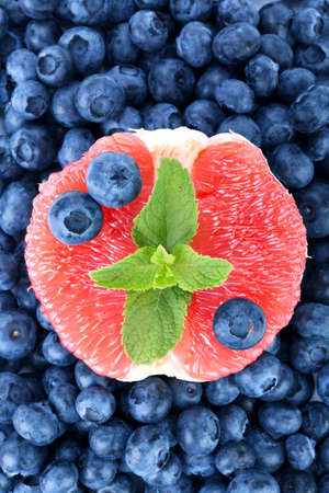 A bitter grapefruit, sweet blueberries and fresh mint as a background. Nutritious citrus in a center of bilberries.
