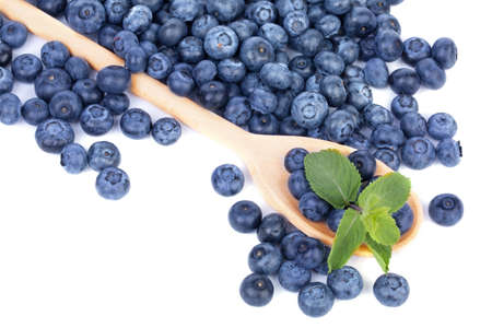A big wooden spoon with organic blueberries and leaves of fresh mint, isolated on a white background. Copy space.