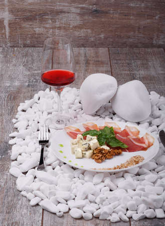 A white plate with prosciutto or balyk, Roquefort cheese, walnuts and bazil, a glass of red wine on a white stone wooden background.