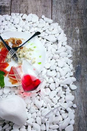 pancetta cubetti: Vista dall'alto di una piastra con prosciutto salato, formaggio, noci e basilico, un bicchiere di vino rosso su una pietra bianca e su uno sfondo in legno.
