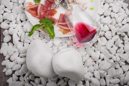pancetta cubetti: Un piatto con carne salata, formaggio, noci e basilico, un popolo e un coltello su pietre bianche e su uno sfondo in legno, vista dall'alto.