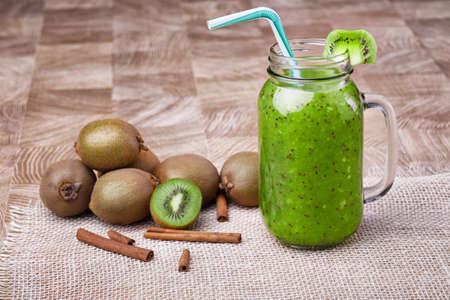 A mason jar full of kiwi smoothie with drinking straw and a slice of kiwi, cinnamon on a light wooden background. Copy space. Stock Photo