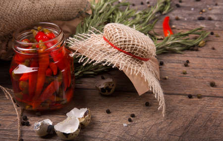 capsaicin: Closeup of spicy chili peppers in a jar, shells of quail eggs and fragrant rosemary on a light wood background.