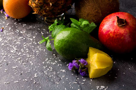 Close-up of fruits on a gray background. A composition of exotic fruits: avocado, garnet, carambola. Cute flowers and mint. Stock Photo