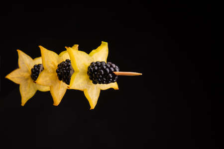 Closeup of a bright yellow wholesome carambola on a stick with a black juicy blackberry on a dark black background.