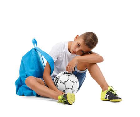 Een leuke jongen met een heldere schooltas en een voetbalbal die op een witte achtergrond wordt geïsoleerd. Een zittend kind. Moe jongen. Ruimte kopiëren. Stockfoto