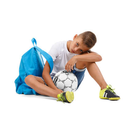 A cute boy with a bright satchel and a soccer ball isolated on a white background. A sitting child. Tired kid. Copy space. Archivio Fotografico