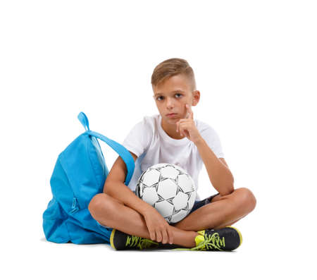 A boy sitting in the lotus position. A sportive kid with bright satchel and soccer ball isolated on a white background. Stock Photo