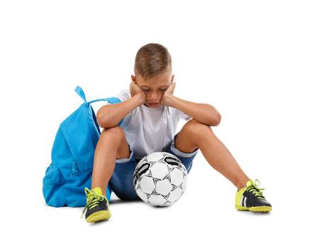 A sad boy isolated on a white background. Tired kid with a bright satchel and a soccer ball. A troubled child. Copy space.