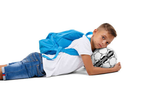 A sportive kid with a bright satchel lying on the ground. A little footballer isolated on a white background.