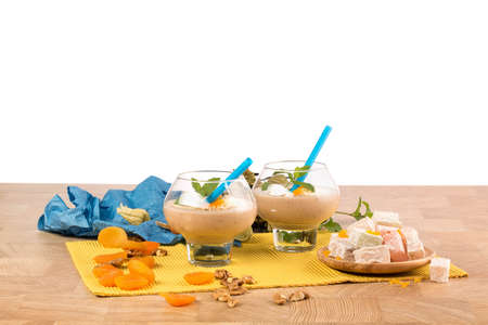 Fruity smoothies in dessert glasses isolated on a white background. Cocktails next to Turkish Delight and dried apricots.