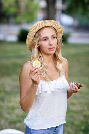 Preety young woman on a garden background. A blonde girl in a hat. A girl with a lemon. Exotic diets. Healthy lifestyle.