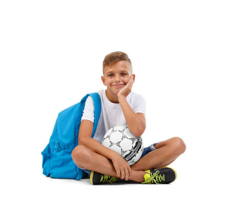 A boy with a soccer ball and a blue satchel sitting in a joga pose. Happy child isolated on a white background. Sports concept.