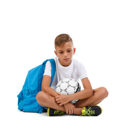 A sad boy isolated on a white background. Tired kid with a bright satchel and a soccer ball. A sitting child. Copy space. Stock Photo