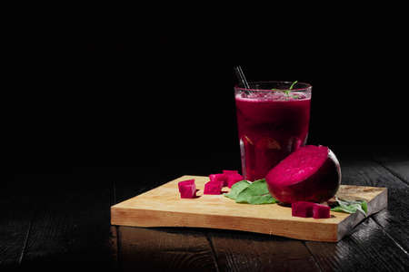 Beautiful composition of veggie drink. Beet smoothie and cut beetroot on a black background. Beet products. Copy space. Banco de Imagens