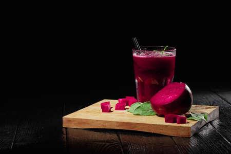 Bela composição de bebida vegetariana. Batido da beterraba e beterrabas cortadas em um fundo preto. Produtos de beterraba. Copie o espaço.