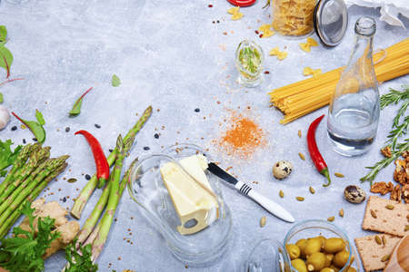 A composition of various healthy ingredients on a gray table background. Greens, asparagus, hot chili pepper, raw pasta, spices and a knife with a butter in a glass box top view. Cooking concept.