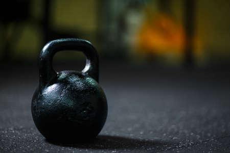 Een close-up van stalen zwarte kettlebell op een wazige achtergrond. Een kettlebell op een fitnessruimte. Kopieer de ruimte.