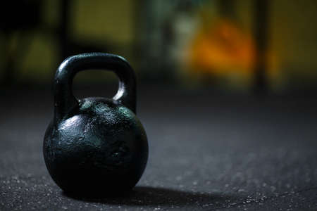 A close-up of steel black kettlebell on a blurred background. A kettlebell on a gym floor. Copy space.