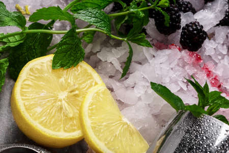 Juicy yellow lemon, sappy green leaves of mint, white pieces of ice and metallic shaker on a colorful background.