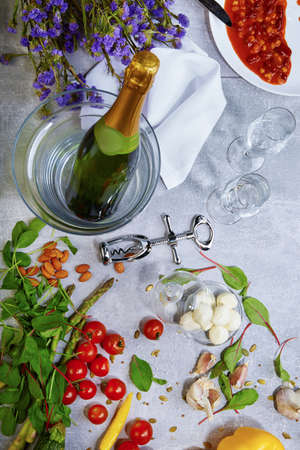 Top view of a gray table with plate, champagne, tomatoes, asparagus, glasses, corkscrew, beans on a gray background.