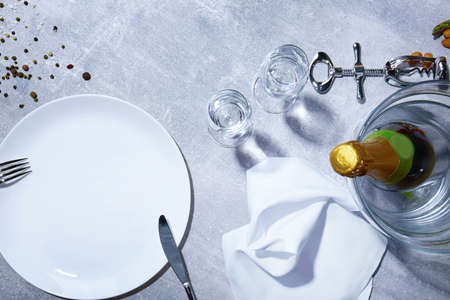 Closeup of white plate, fork, knife, green bottle of champagne, glasses, seasonings on a gray background. Stock Photo
