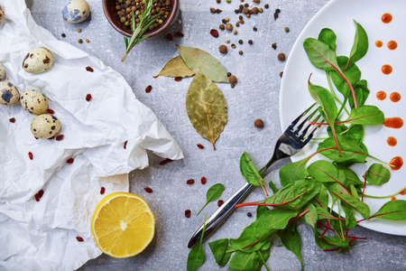 Closeup of a table with bay leaves, green salad leaves, quail eggs, a half of lemon on a light gray background.