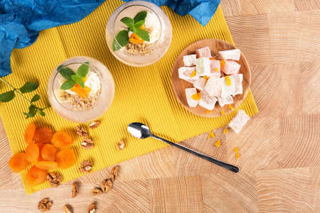 colored bottle: Summer banana smoothies in a huge glasses with Turkish Delight, dried apricots and walnuts on multi-colored background, top view.