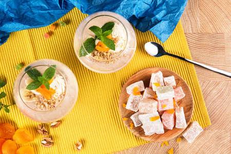 Deux smoothies fruité dans des verres de dessert avec des bonbons et des fruits sur un fond jaune. papaye rustique et raisins secs avec des abricots secs sur une chaude noix de coco . vue de dessus Banque d'images - 83954728