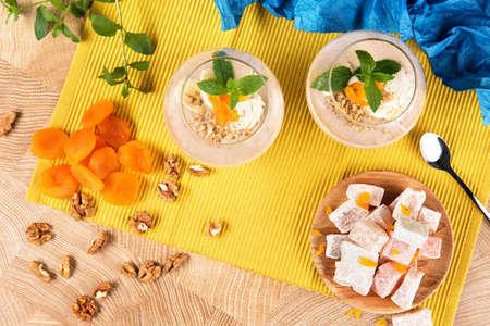 Vue de dessus des smoothies à la banane dans un grand verre avec délice turc, abricots secs et noix sur un fond multicolore. Banque d'images - 84000302
