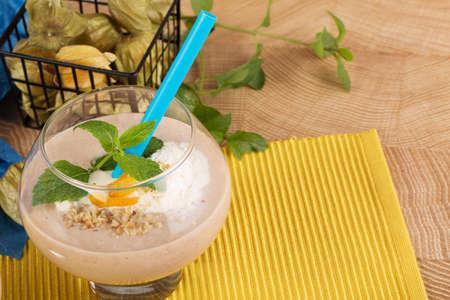 Smoothie fruité dans un verre à dessert avec de la paille bleue sur fond jaune. Cocktails avec abricots secs, glaces et bananes, gros plan. Banque d'images - 84000303