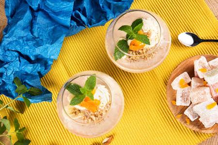 Smoothies banane d'été dans un grand verre avec Turkish Delight, abricots secs et noix sur un fond multicolore, vue de dessus. Banque d'images - 84000305