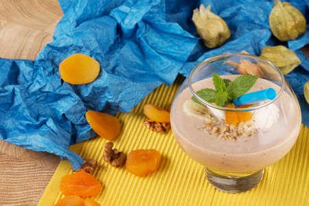 Smoothie fruité dans un verre à dessert avec de la paille sur un fond jaune et bleu. Cocktails avec abricots secs, glaces et bananes, gros plan. Banque d'images - 84000306