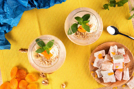 colored bottle: Top view of two banana smoothies in a huge glasses with Turkish Delight, dried apricots, walnuts and spoon on multi-colored background. Healthy smoothie with sweets. and fruits.