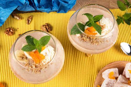 Vue de dessus de deux smoothies à la banane dans un grand verre avec Turkish Delight, abricots secs, noix et cuillère sur fond multicolore Smoothie en bonne santé avec des bonbons. et fruits, gros plan. Banque d'images - 83954740