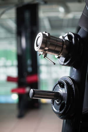 Metal barbell clamps on a holder. Dumbbell clampings on a blurred gym background. Gym equipment. Weightlifting workout. Stock Photo