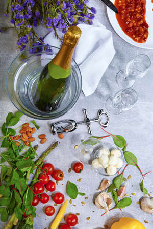 Closeup of a gray table with plate, champagne, tomatoes, asparagus, glasses, corkscrew, beans on a gray background.