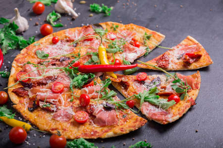 Close-up of a tasty pepperoni pizza with red hot chili pepper, meat, and spices on a dark stone background. Salad leaves, cherry tomatoes, garlic and peppercorns near a yummy meaty pizza.