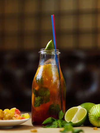 A glass bottle with a refreshing cool beverage, a slice of fragrant lime with a plate of raisins on a blurred background.