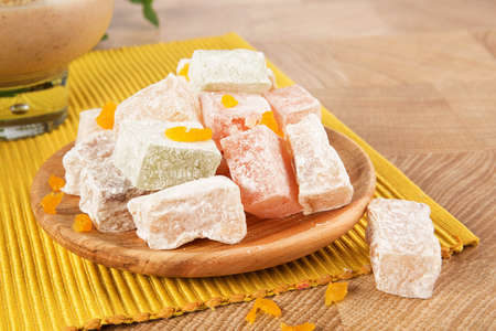 Close-up of a powdered turkish delight. Plate of fruit rahat lokum on a wooden background. Exotic confectionery sweets.