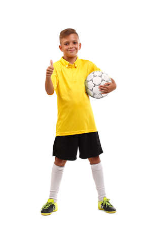 A happy boy with a soccer ball and in a football uniform isolated on a white background. Full-length photo.