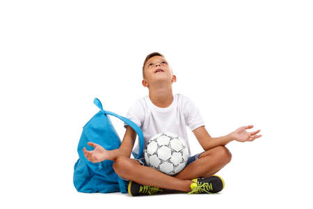 A little boy with a ball sitting in a yoga pose isolated on a white background. A footballer prays for the victory. Stock Photo