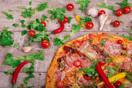 Hot prosciutto pizza on a rustic table background. Whole Italian pizza with vegetables and pepperoni. Italian cuisine. Stock Photo